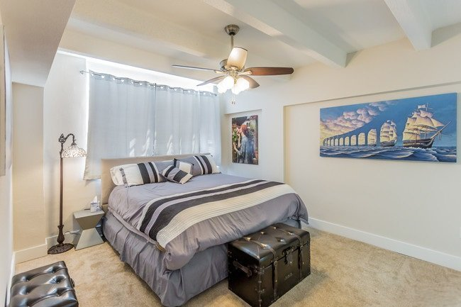 Kira bedroom with a king size bed, ample room, and ceiling fan.