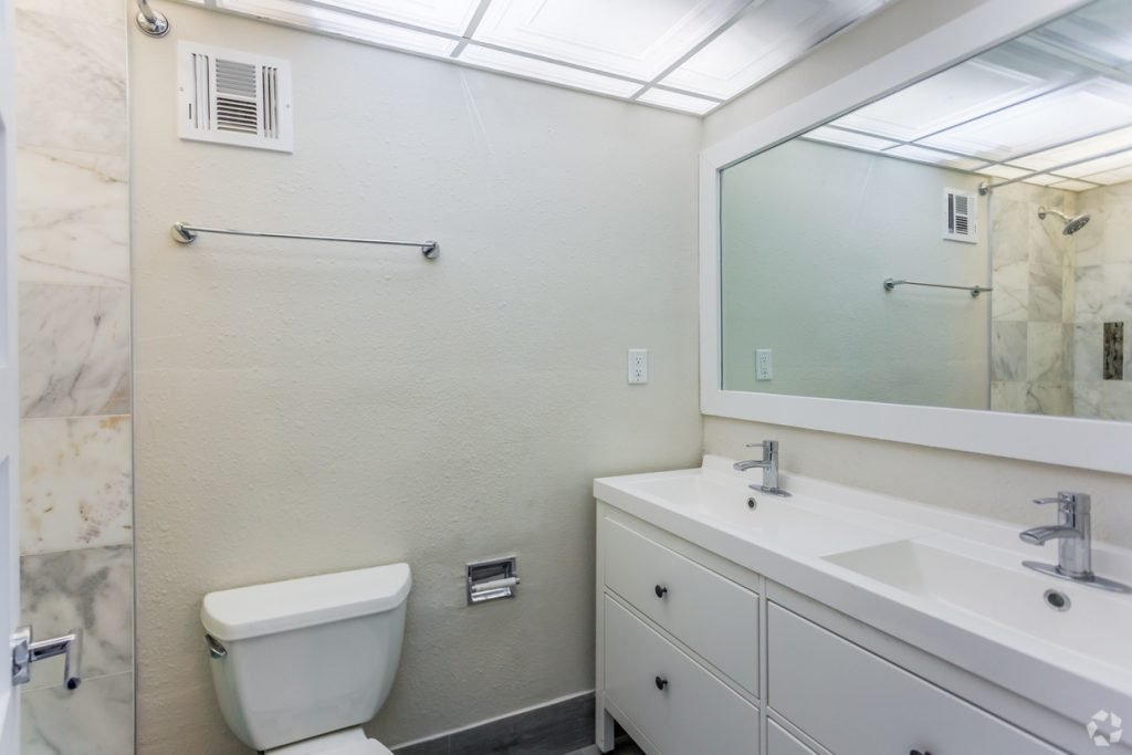 The Pat bathroom with two sinks and a wide vanity mirror