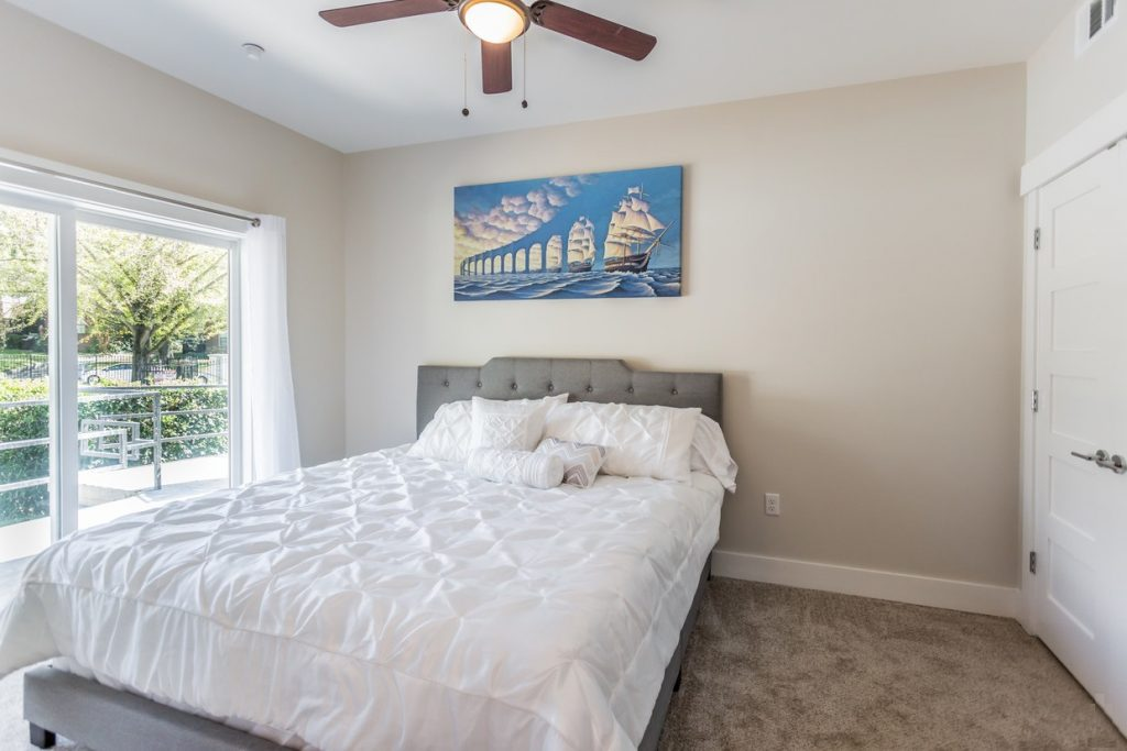 The Ramona's bedroom with a large bed, ceiling fan, and door to the balcony